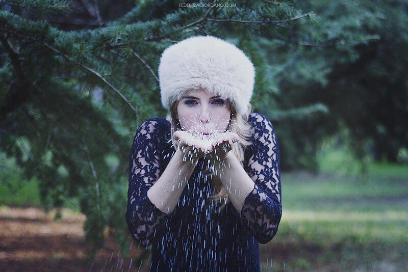 portrait of woman blowing snow