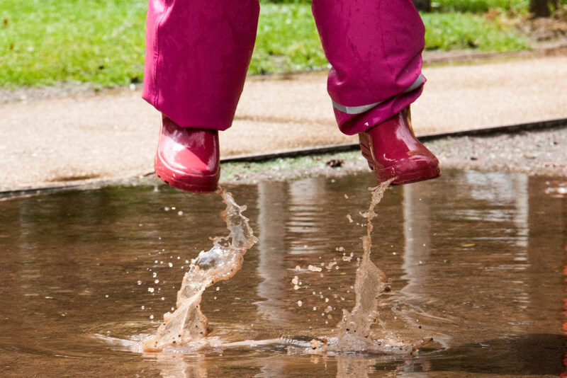 girl jumping in puddle
