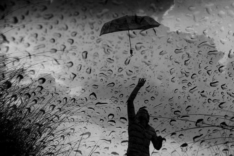 person losing umbrella in the rain