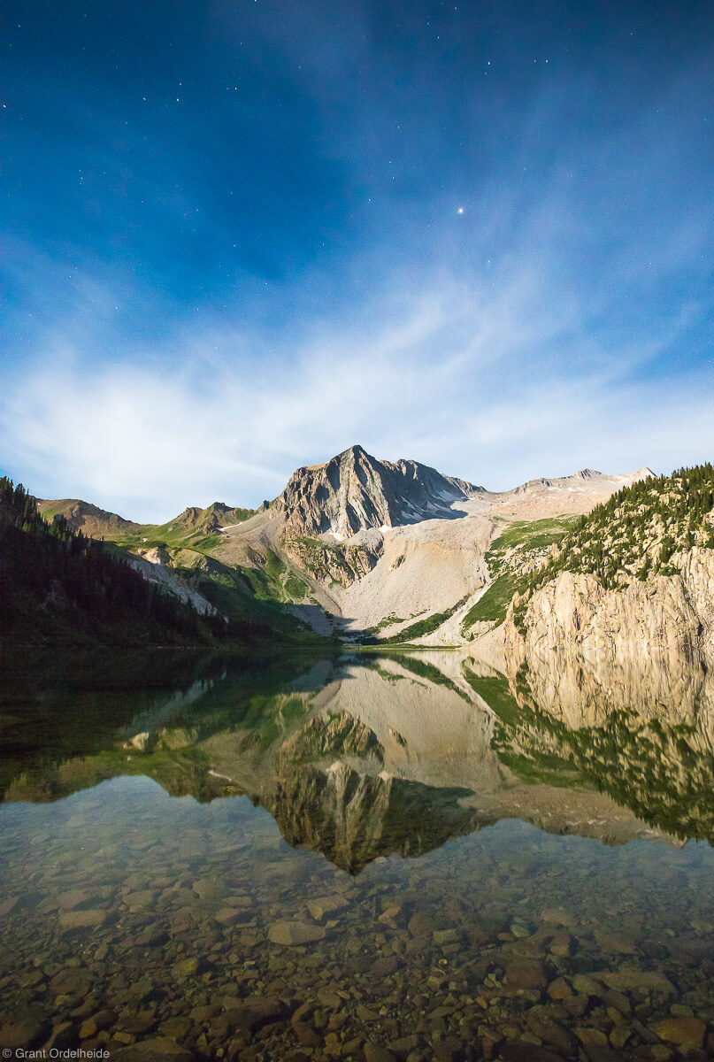 Snomass peak reflected in Snowmass lake illuminated by moonlight.