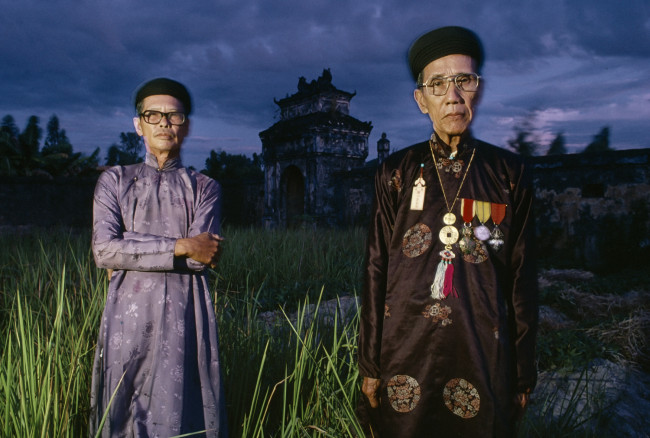 Last of the dying aristocracy: Relatives of Emperor Bảo Đại, stand in their weed-choked garden. Huế, Vietnam, July 1990.