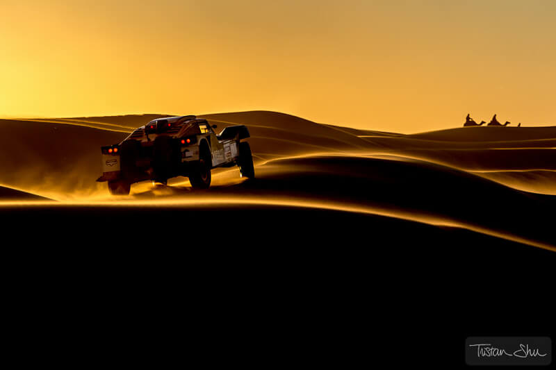 car racing through the Merzuga Desert with camels in the distance