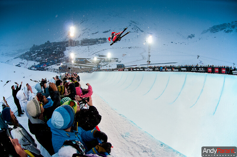 skier jumping in the half-pipe with audience