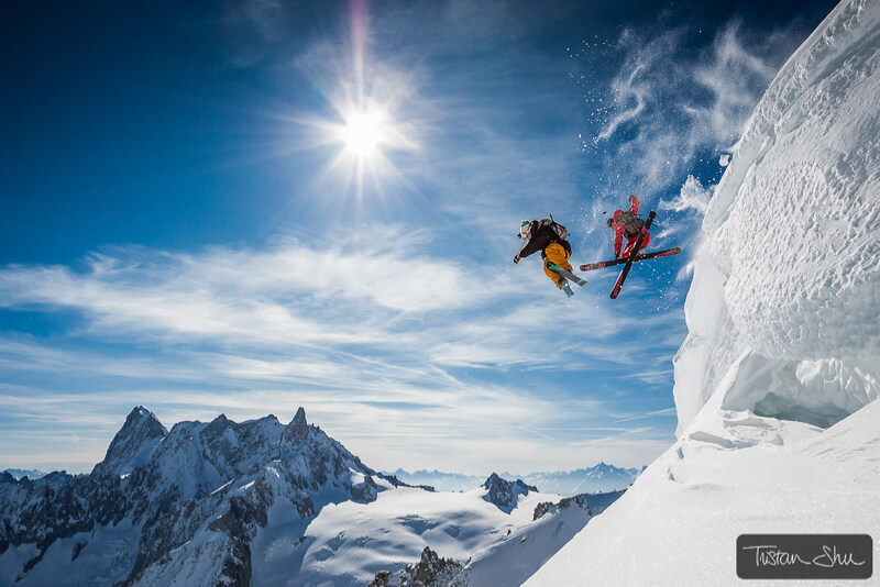 Two skiers jumping off a cliff