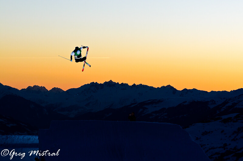 Skier jumping at sunset with mountains in the background