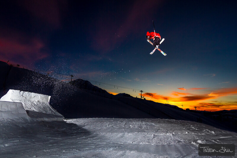 Skier doing a tail grab at sunset