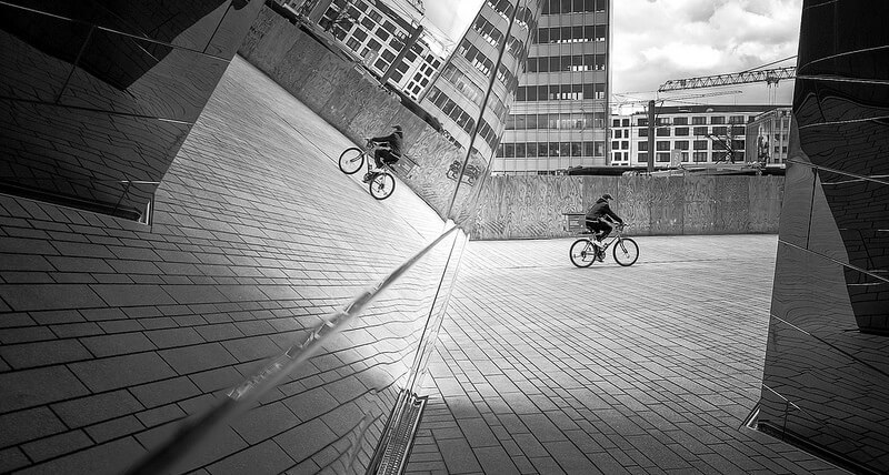 cyclist reflected in a glass building