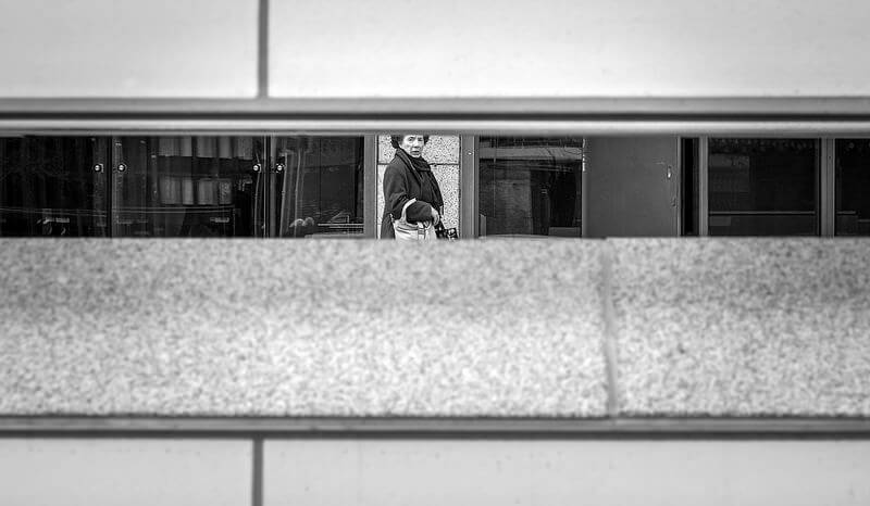 woman in a metro station viewed through a gap