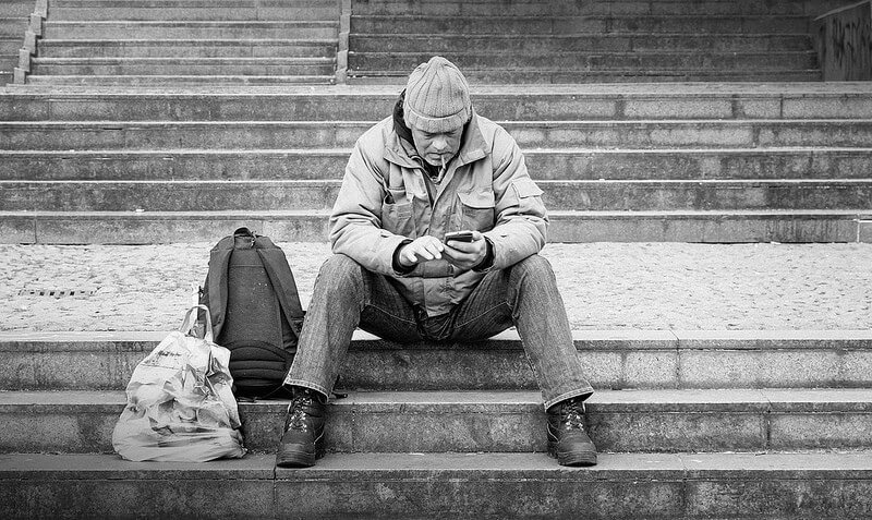 Man using his phone sitting on a staircase