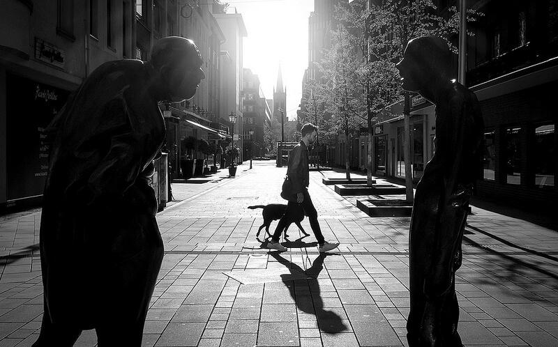 man walking his dog seen between statues