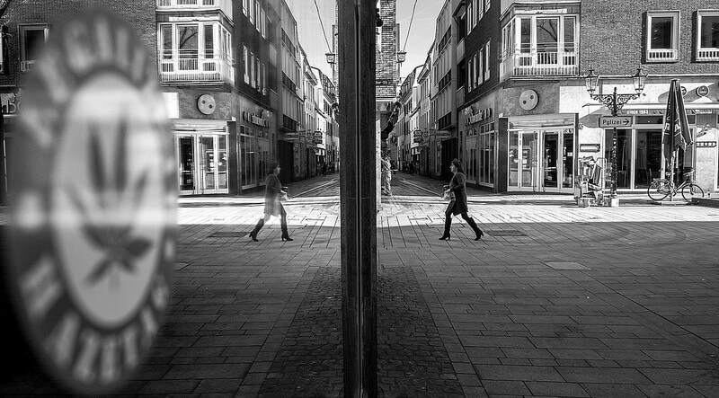 woman walking on the street with her reflection in a window