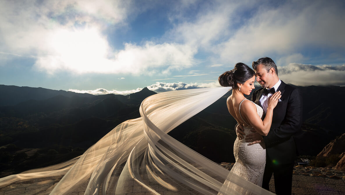 bride and groom pose with veil spread out