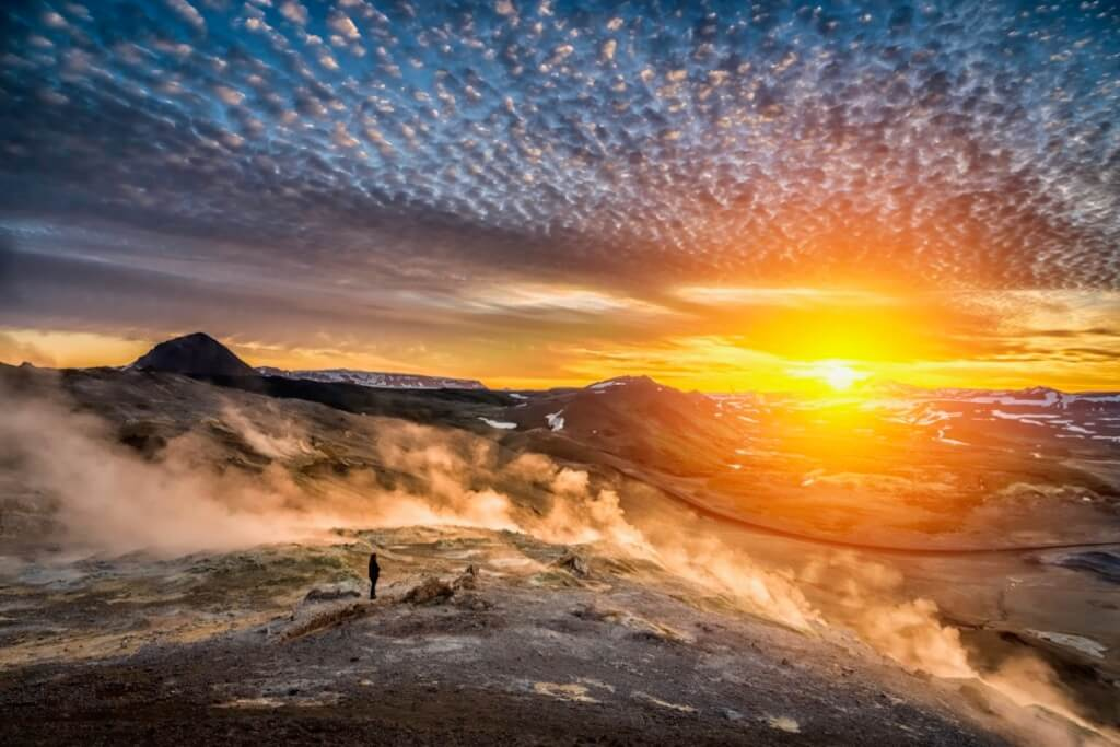 Ragnar TH Sigurdsson - Woman enjoying the mid summer light, midnight sun, Leirhnukur geothermal hot spring area, Mt. Namafjall, Northern Iceland