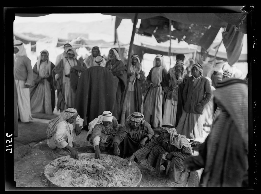 Bedouins eating around large tray in Shunet Nimrin