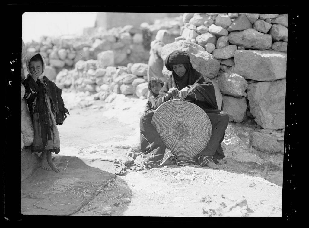 Woman weaving a straw mat