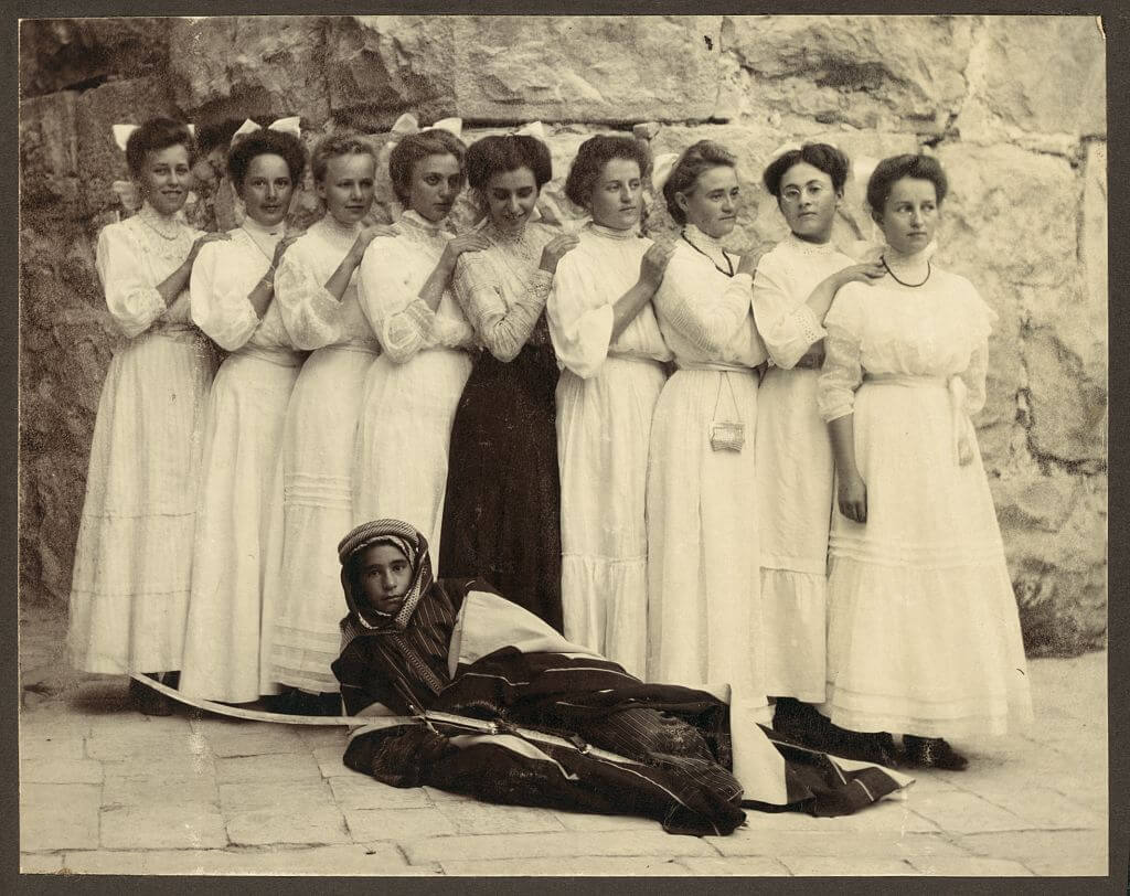 Nine girls standing over young boy holding sword