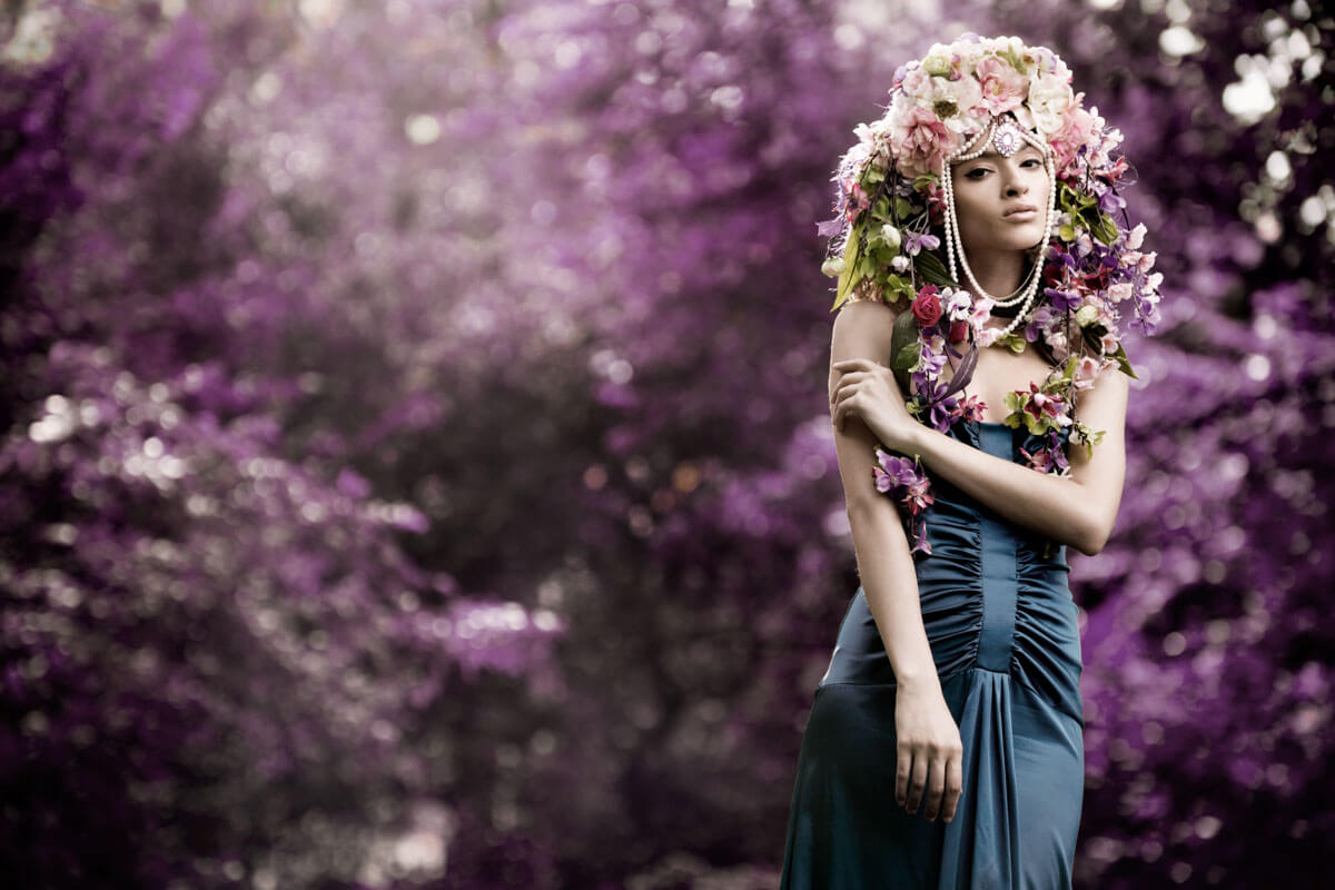 portrait of a floral goddess in front of more flowers
