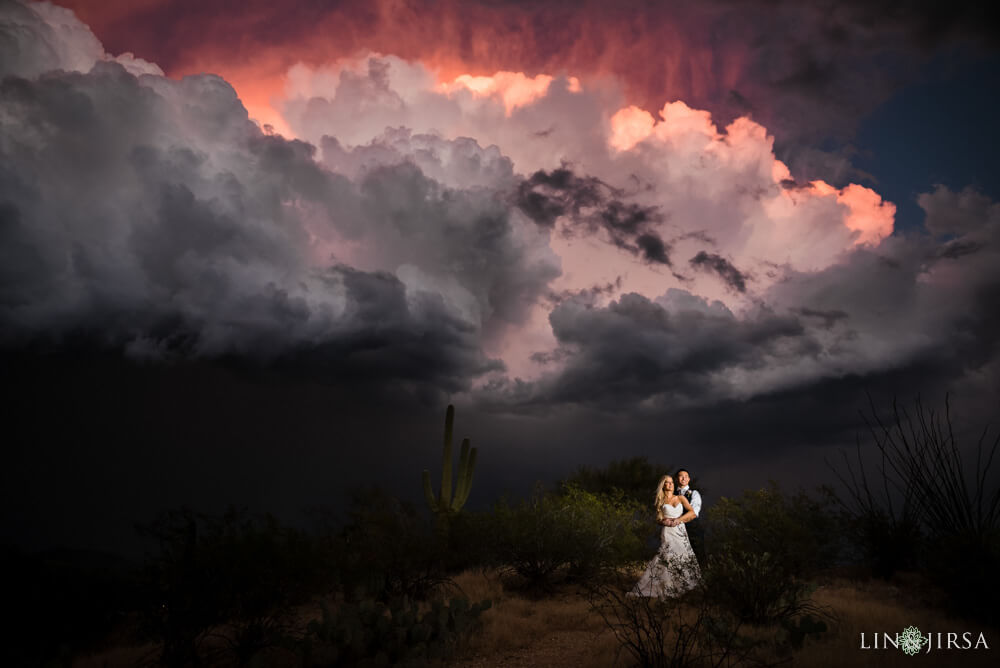 Couple poses under a cloudy sky