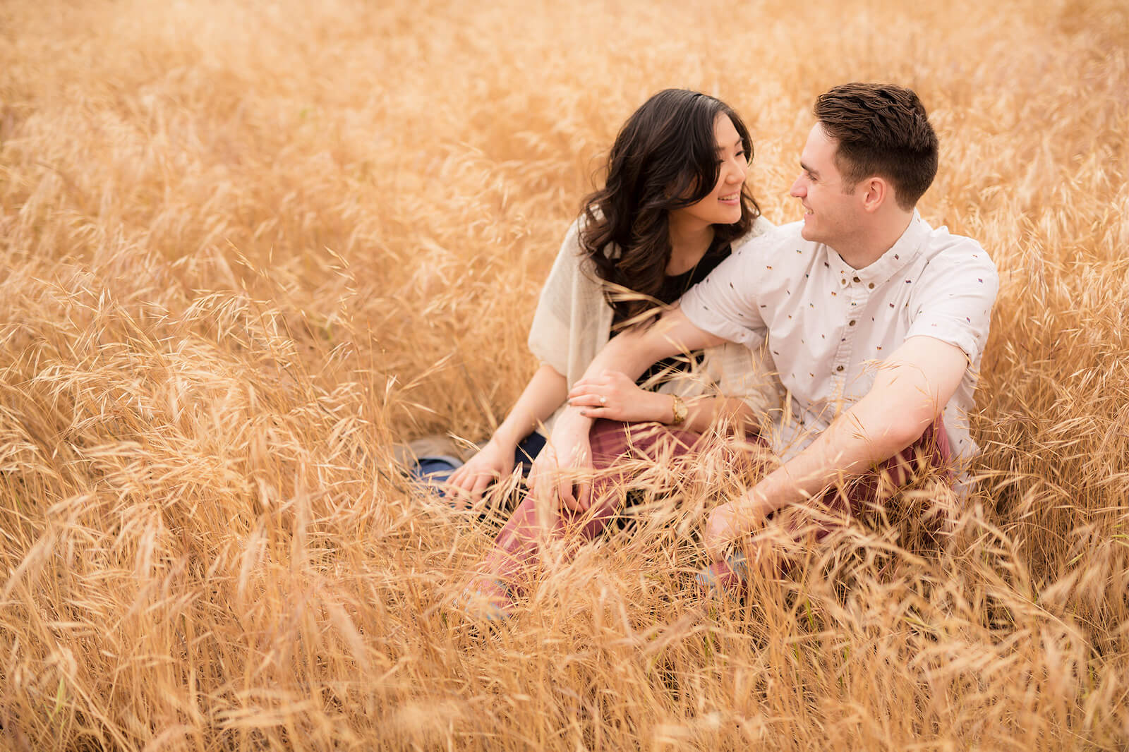 couple sits in field under overcast sky as best time to take photos outside