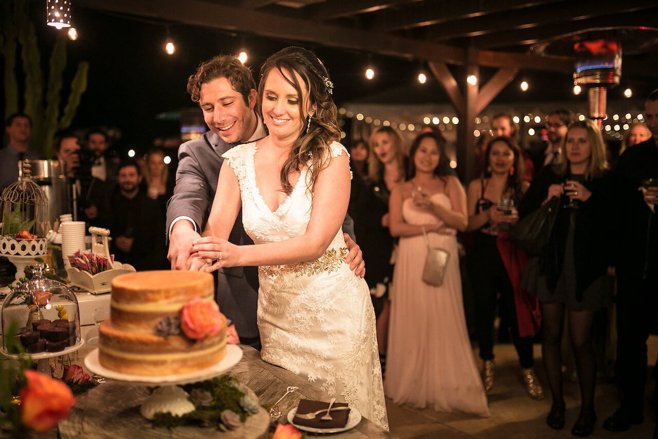 couple cuts cake for wedding cake pictures